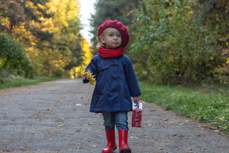 Happy autumn. Little girl in a red beret walking in autumn park. Copy space.
