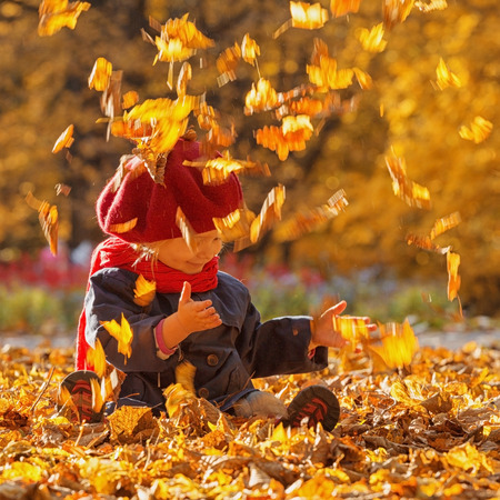Happy autumn. A little girl in a red beret is playing with falling leaves and laughing. Stock Photo
