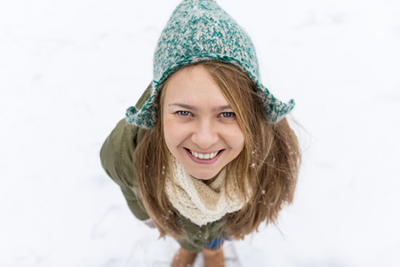 A young beautiful girl with long blond hair enjoys the first snow. Green jacket, green hat and gloves. Top view. Copy space. 免版税图像