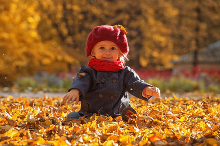 Happy autumn. A little girl in a red beret is playing with falling leaves and laughing. Stockfoto