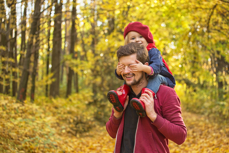 Happy family! The girl closes her dad's eyes with her hands on autumn walk.