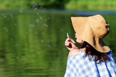 Young woman in a dress and a straw hat blowing bubbles against the background of the river. Back view. Stockfoto