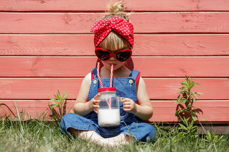 Liittle girl in dungarees and sunglasses with glasses drinks milk from a jar. Copy space, toned.
