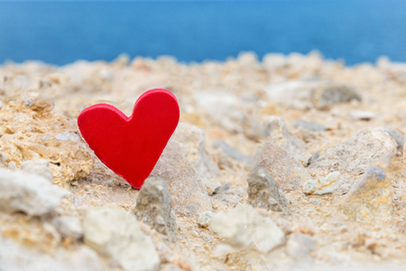 Red heart on the background of the sea. The concept of holiday love.