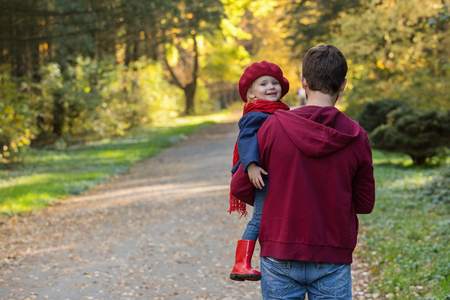 Father hugs daughter in autumn day. Back view, copy space.