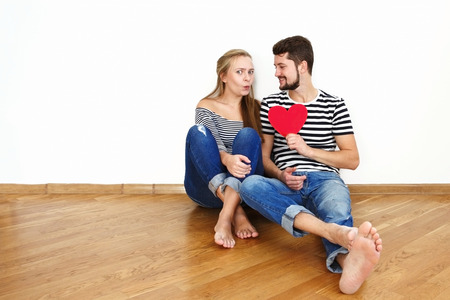 Happy young couple in love sitting on the floor in their apartment Stock Photo