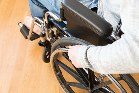 Detail of disabled man hand holding wheel of a wheelchair.