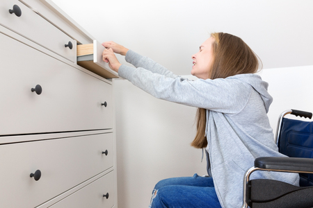 Young disabled woman in  wheelchair opens drawers in the dresser. Reklamní fotografie