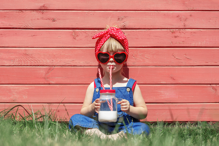 Little girl in dungarees and sun glasses is drinking milk. Colorful summer concept. Copy space. Stockfoto