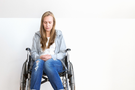 Depressed young woman is sitting on wheelchair at modern room.