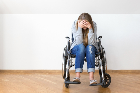 Depressed young woman in wheelchair. Without face, copy space. Reklamní fotografie