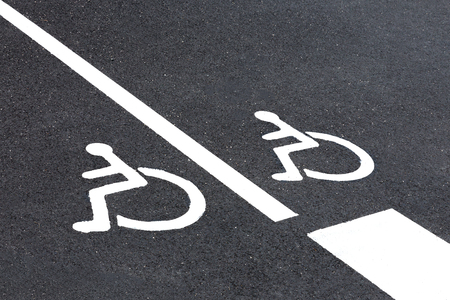 Disabled sign painted on grey asphalt.