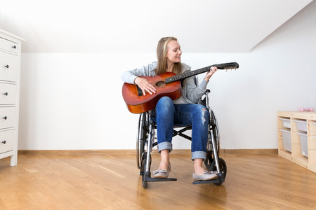 Handicapped woman learning play the guitar. Reklamní fotografie