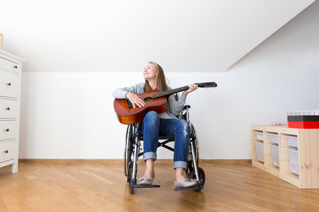 Young disabled woman playing the guitar.