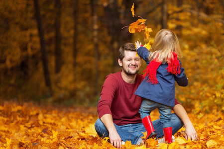 Father and daughter throw leaves in the autumn park.