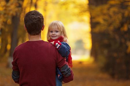 Dad hugs a little daughter in an autumn park. 版權商用圖片