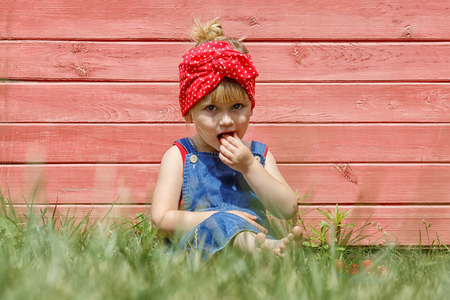 Little girl in dungarees is eating strawberries in the garden. Sunny summer. Copy space.