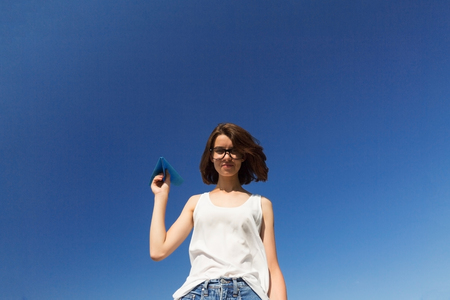 Teenager girl is throwing a paper plane. Blue sky background, copy space.