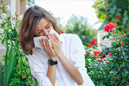 Young girl blowing nose in garden. Spring allergy concept.