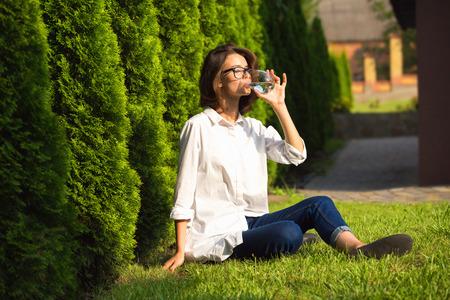 Mujer joven bebe agua en el jardín
