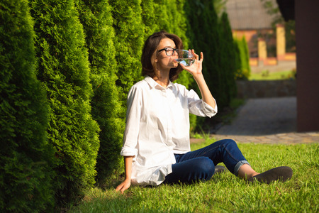 Young woman drinks water in garden