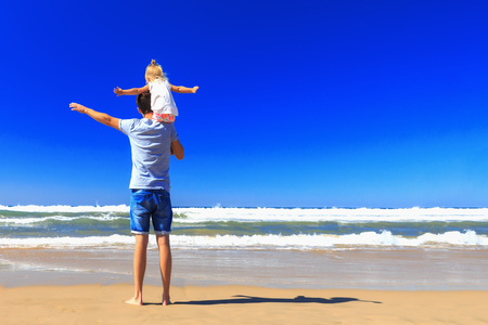 Father holds his daughter on his shoulders on the sea shore on a sunny day. Stockfoto