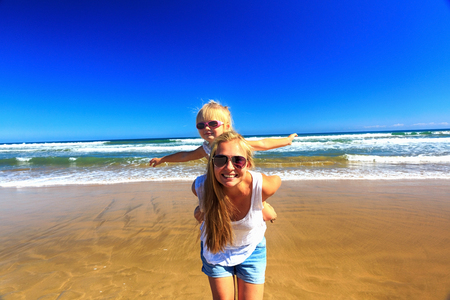 Happy mother and daughter spend their holidays on the seashore.