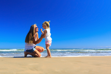 Happy mother and daughter having fun on the seashore.