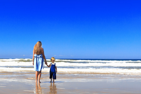 Happy Mother and daughter are walking on the beach. Back view, copy space.