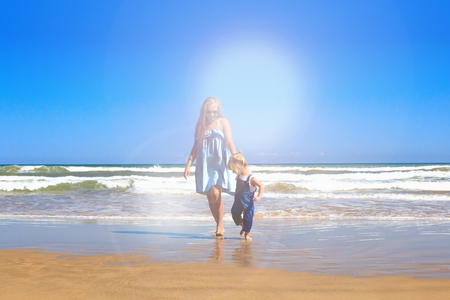 Mother and daughter are walking on the beach. Front view, copy space.