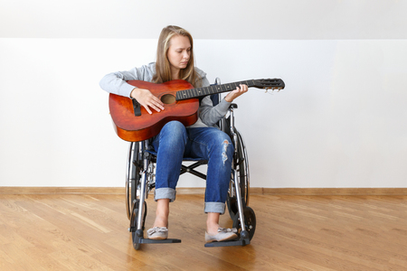 Disabled young woman in wheelchair playing the guitar
