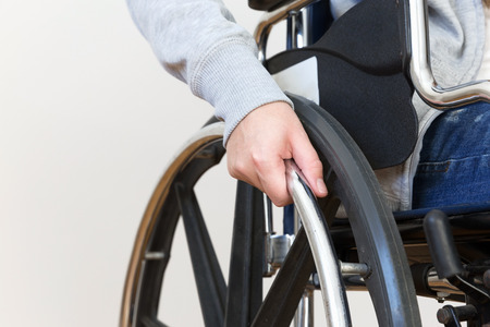 Detail of disabled woman holding a hand on wheel of a wheelchair. Close up.