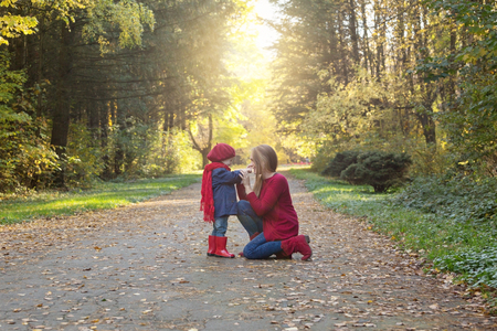 Happy family! Mother and daughter spend time in the autumn park. Laugh and play.