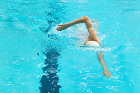 A teenage athlete is swimming crowl. Without face, selective focus.