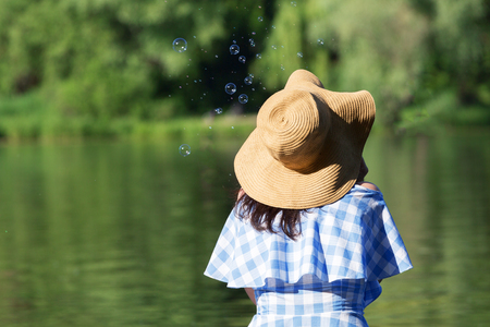 Young woman in a dress and a straw hat blowing bubbles against the background of the river. Back view. 免版税图像