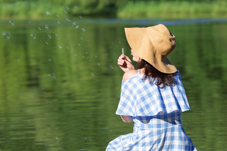 Young woman in a dress and a straw hat blowing bubbles against the background of the river. Back view. Stock Photo