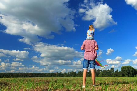 Dad holds his daughter on his shoulders and they will fly a kite. 版權商用圖片