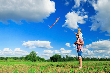 Happy family. Father and daughter are flying a kite in the field.