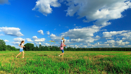 Happy family. Mother, father and daughter are flying a kite in the field.