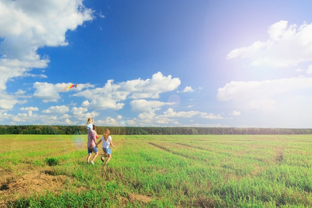 Happy family. Mother, father and daughter are flying a kite in the field. back view, copy space.
