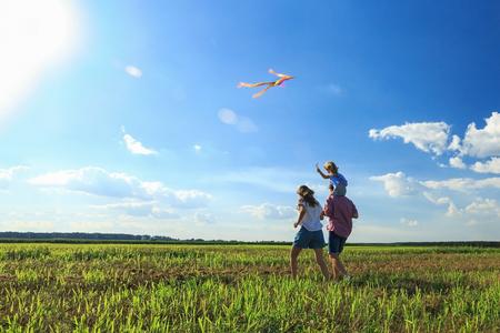 Familia feliz. Madre, padre e hija están volando una cometa en el campo. vista posterior, copie el espacio. Foto de archivo