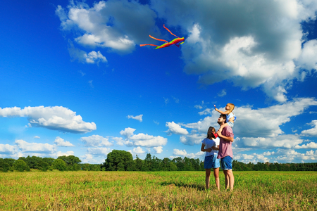 Happy family. Mother, father and daughter are flying a kite in the field. Front view, copy space. Stockfoto