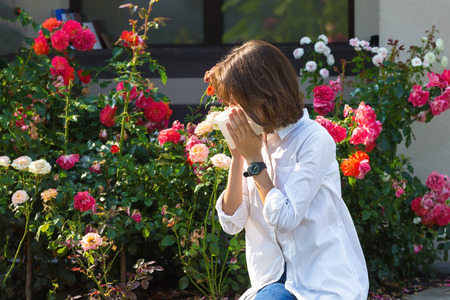 Beautiful young woman blowing nose in garden. Allergy concept.