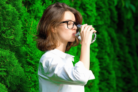 Mujer joven bebe agua