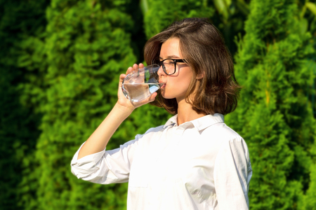 Young woman drinks water in garden Stockfoto