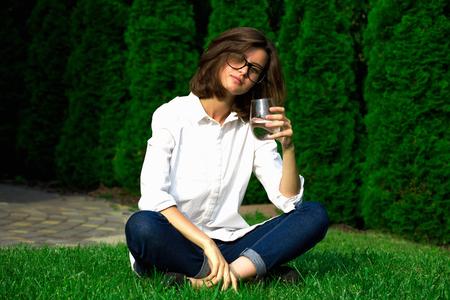 Sitting girl drinks water in the garden.
