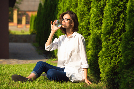 Young woman drinks water in garden Stockfoto - 122904678