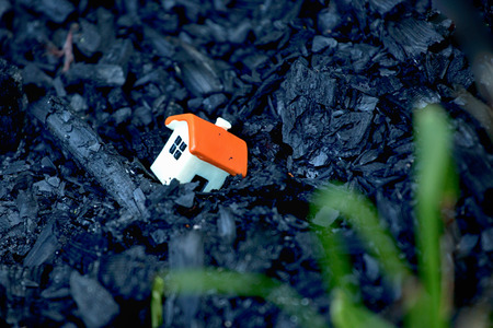 Small toy house lies on coals. Disaster concept.