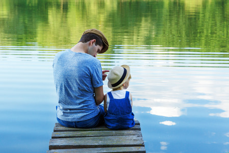 Dad and a tiny girl in dungarees relax at the river. Back view, copy space. Stockfoto