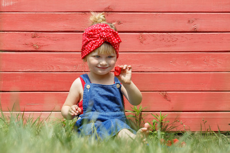 Little girl is eating sweet strawberries on a sunny day. Copy space. Stockfoto